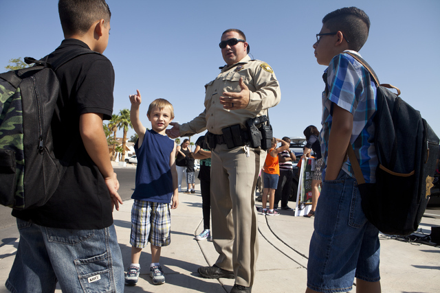 Las Vegas police officer Daryl McDonald speaks to students including, Josiah Jackson, center and Mark Fotan, right, about safety while crossing the street at the C.H. Decker Elementary School on T ...