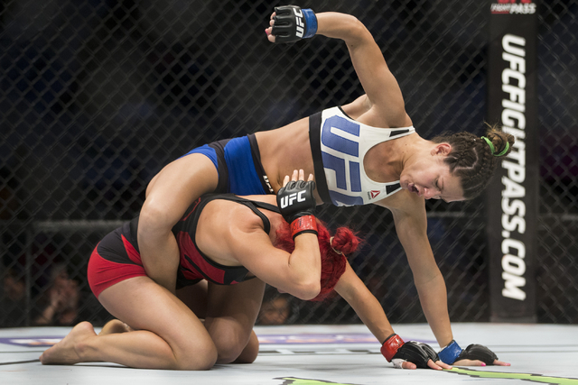 Cortney Casey, top, throws a punch against Randa Markos in the women's strawweight bout during UFC 202 at T-Mobile Arena on Saturday, Aug. 20, 2016, in Las Vegas. Casey won by a first round submis ...