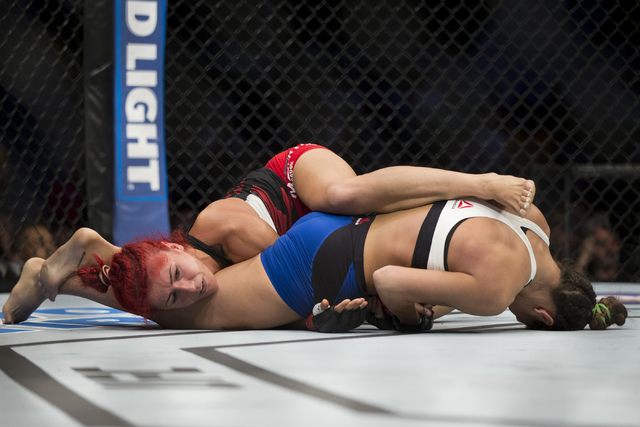 Cortney Casey, right, locks an arm bar to win by way of submission in the first round against Randa Markos in the women's strawweight bout during UFC 202 at T-Mobile Arena on Saturday, Aug. 20, 20 ...