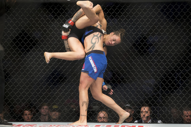 Elizabeth Phillips, is taken down by Raquel Pennington in the women's bantamweight bout during UFC 202 at T-Mobile Arena on Saturday, Aug. 20, 2016, in Las Vegas. Pennington won by unanimous dec ...