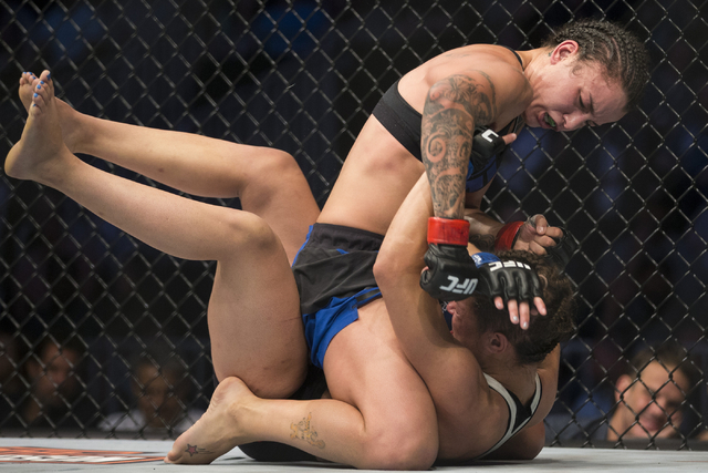 Elizabeth Phillips, top, connects punches against Raquel Pennington in the women's bantamweight bout during UFC 202 at T-Mobile Arena on Saturday, Aug. 20, 2016, in Las Vegas. Pennington won by  ...