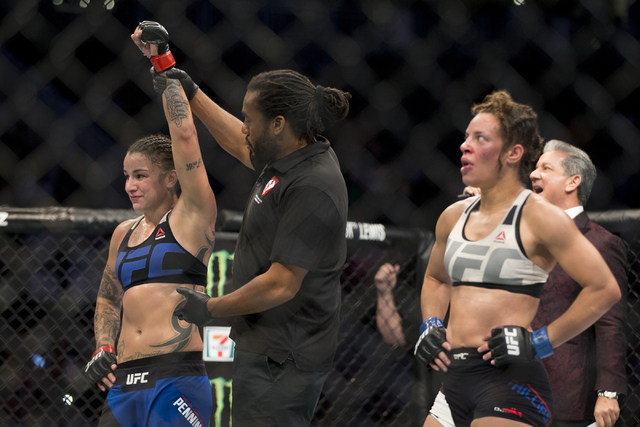 Elizabeth Phillips, left, raises her arm in victory against Raquel Pennington in the women's bantamweight bout during UFC 202 at T-Mobile Arena on Saturday, Aug. 20, 2016, in Las Vegas. Penningt ...