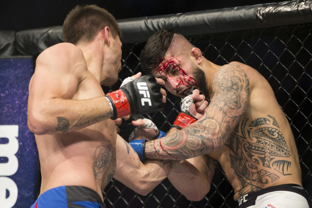 Tim Means, left, throws a punch against Sabah Homasi in the welterweight bout during UFC 202 at T-Mobile Arena on Saturday, Aug. 20, 2016, in Las Vegas. Means won by technical knockout in the seco ...