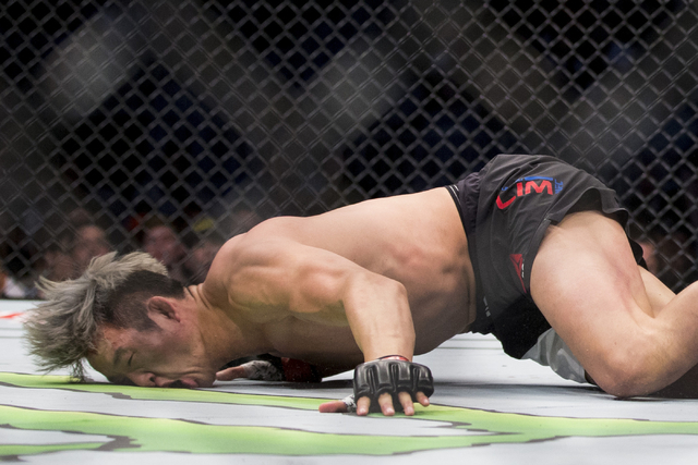 Hyun Gyu Lim, left, falls on his face after getting punched by Mike Perry in the welterweight bout during UFC 202 at T-Mobile Arena on Saturday, Aug. 20, 2016, in Las Vegas. Perry won by a first r ...