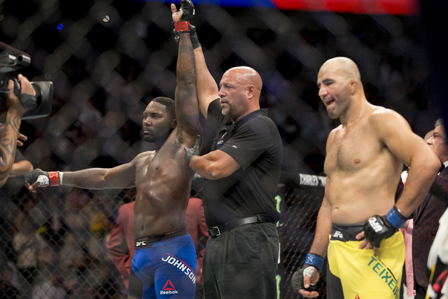 Anthony Johnson, left, raises his arm in victory after his first round knockout win against Glover Teixeira in the light heavyweight bout during UFC 202 at T-Mobile Arena on Saturday, Aug. 20, 201 ...