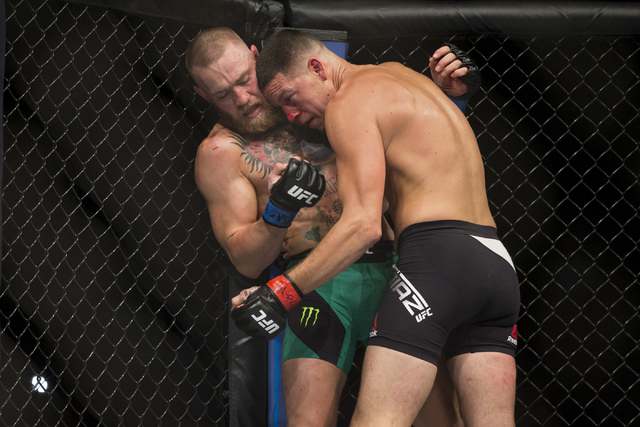 Conor McGregor, left, battles Nate Diaz in the welterweight bout during UFC 202 at T-Mobile Arena on Saturday, Aug. 20, 2016, in Las Vegas. McGregor won by majority decision.  (Erik Verduzco/Las V ...