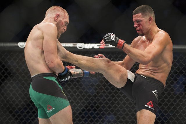 Nate Diaz, right, connects a kick against Conor McGregor in the welterweight bout during UFC 202 at T-Mobile Arena on Saturday, Aug. 20, 2016, in Las Vegas. McGregor won by majority decision.  (Er ...