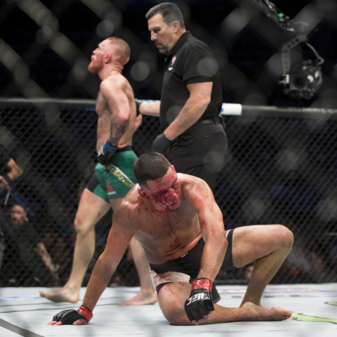 Nate Diaz, left, gets up after being taken down in the last second of the round against Conor McGregor in the welterweight bout during UFC 202 at T-Mobile Arena on Saturday, Aug. 20, 2016, in Las  ...