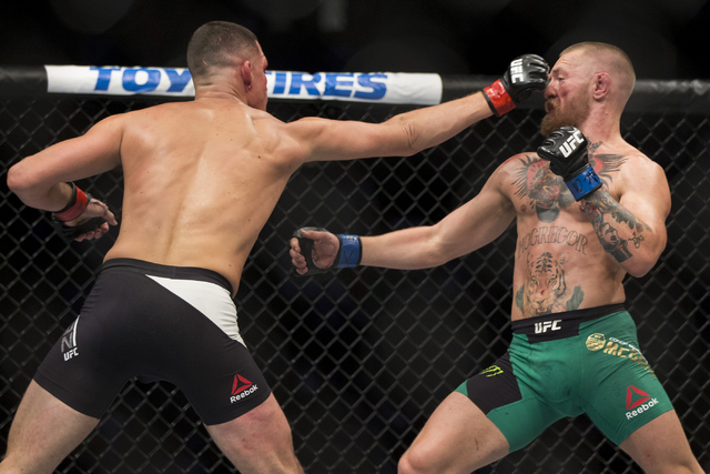 Nate Diaz, left, throws a punch against Conor McGregor in the welterweight bout during UFC 202 at T-Mobile Arena on Saturday, Aug. 20, 2016, in Las Vegas. McGregor won by majority decision. Erik V ...