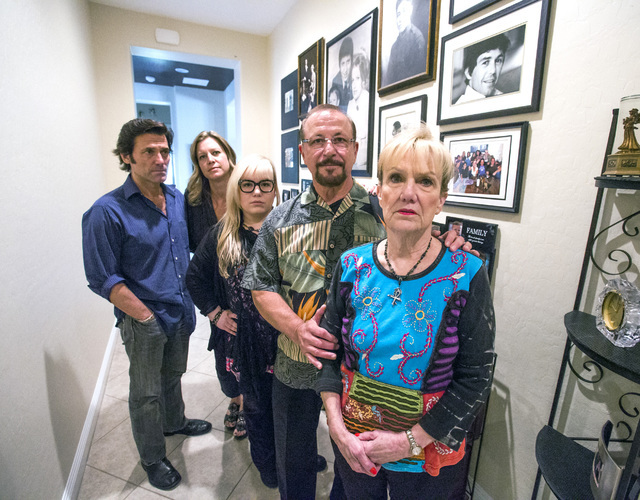 The family of murder victim Jay Sebring stands next to the wall of family portraits in the DiMaria'sHenderson home. On the right is Sebring's sister Peggy DiMaria, flanked by her husband, Tony, an ...