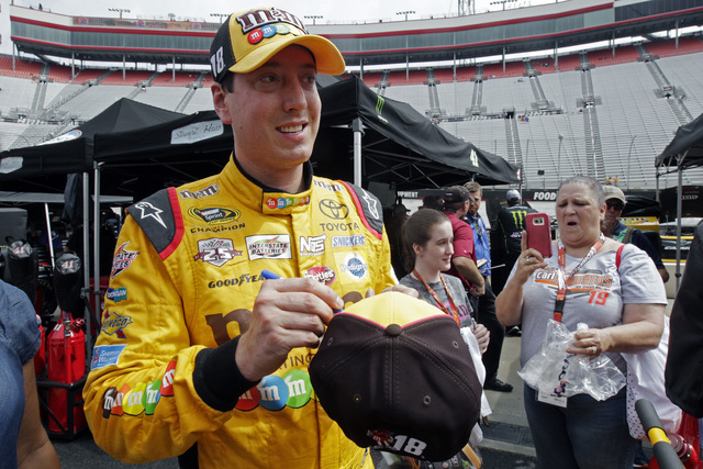 Kyle Busch signs an autograph as he walks through the pit area after practice for a NASCAR Sprint Series auto race on Friday, Aug. 19, 2016, in Bristol, Tenn. (AP Photo/Wade Payne)