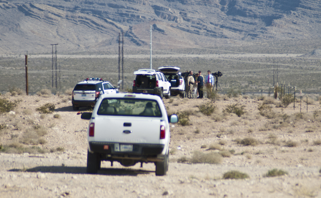 A police officer directs media away from a dirt road near Nellis Air Force Base on Thursday morning, Aug. 18, 2016. A media briefing detailed the crash of an Air Force plane earlier this morning d ...