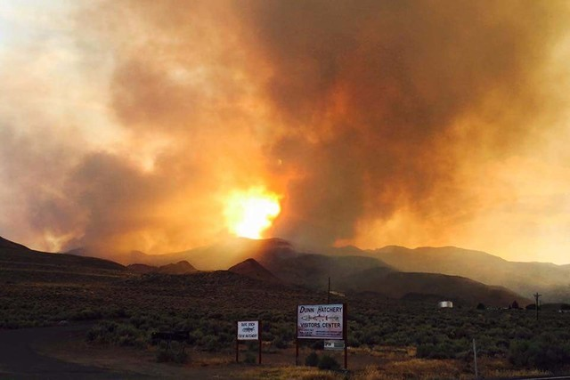 Smoke and flames are visible from a wildfire burning in the community of Sutcliffe, about 35 miles north of Reno, Friday, July 29, 2016. The wildfire was deterred Sunday from burning the tribal to ...
