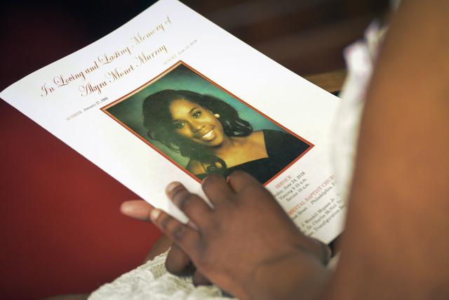 A mourner holds a funeral service program for Akyra Murray at Philadelphia's Monument Baptist Church. A high school basketball coach raised $15,297 via the GoFundMe for Akyra's family. (Raymond Ho ...