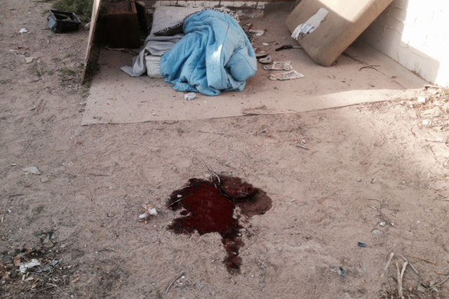 A pool of blood near a makeshift bed is seen Monday, March 10, 2014 behind a building at 800 N. Tonopah after David Robinson was killed in an officer-involved shooting in North Las Vegas. A civil  ...