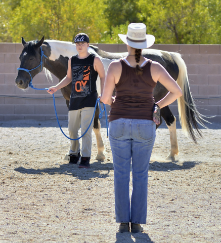 Equestrian specialist Heather Medford, right, watches as Adam Moericke works with Oreo at the Goals4Success equine therapy ranch at 5138 N. Juliano Road in Las Vegas July 23. Bill Hughes/View