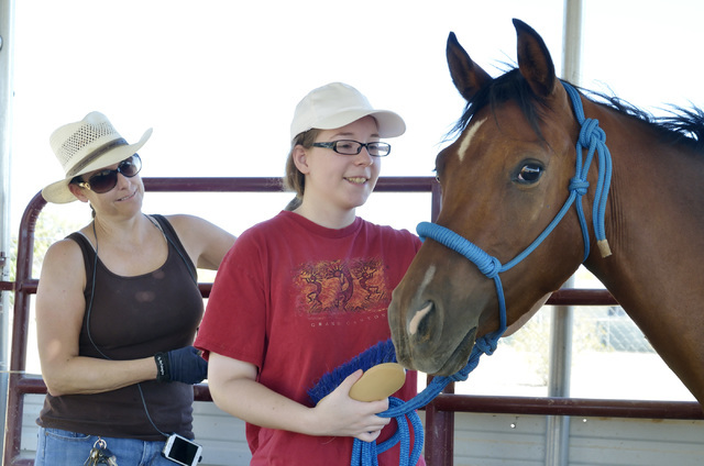Equestrian specialist Heather Medford, left, watches as Jade Cottonwood works with Baby at the Goals4Success equine therapy ranch at 5138 N. Juliano Road in Las Vegas July 23. Bill Hughes/View