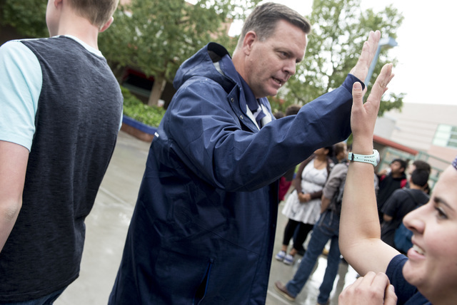 Shadow Ridge High School principal Travis greets students with high-fives as they make their way to lunch. Warnick was named a finalist of Varsity Brands 2016 School Spirit Awards Principal of Pri ...