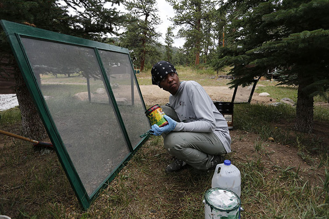 Tatyana Mosley, a crew member for the nonprofit organization Rocky Mountain Conservancy, helps restore old cabins used by research scientists inside Rocky Mountain National Park, near Estes Park,  ...