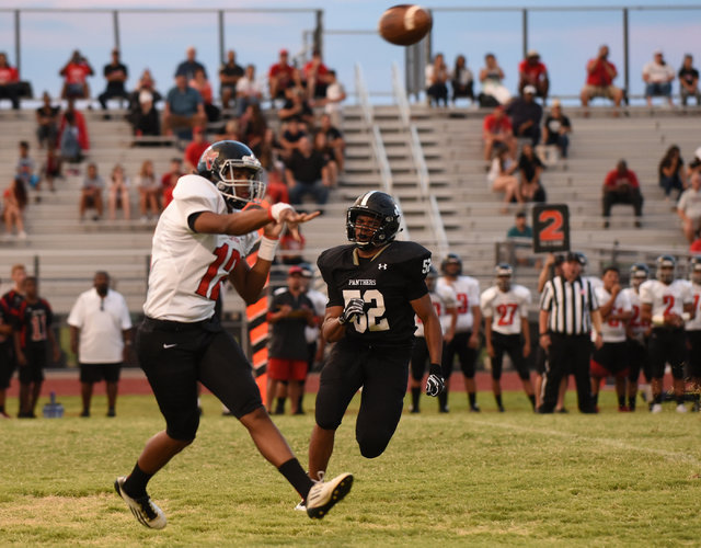 Las Vegas high's Zach Matlock (12), left, throws a pass against Palo Verde's Hunter Winstead during their football game playe at Palo Verde's football field in Las Vegas on Friday, Aug. 26, 2016.  ...