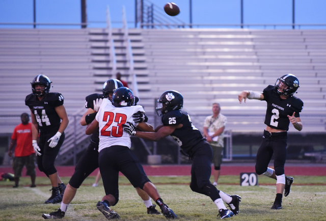 Palo Verde's Jonathan Schofield (2), right, throws a pass against Las Vegas High School's defense during their football game played at Palo Verde's football field in Las Vegas on Friday, Aug. 26,  ...