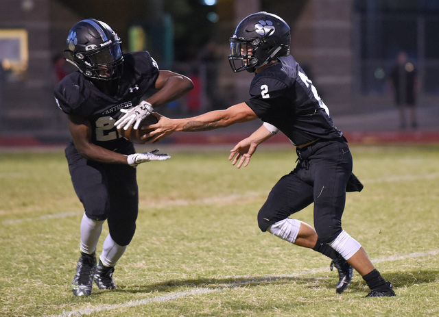 Palo Verde's Jonathan Schofield (2), right, hands off the football to teammate Chamere Thomas (22) against Las Vegas High School's defense during their football game playe at Palo Verde's football ...