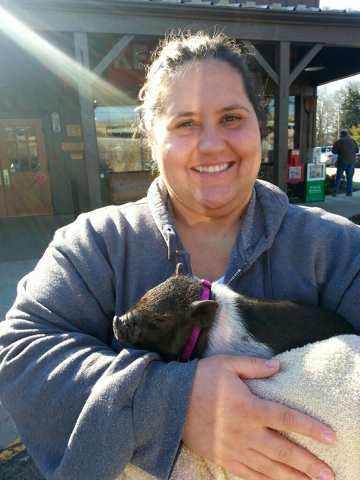 Katie Manni of Aliquippa, Pa., holds her Vietnamese potbellied pig named Charlotte in the parking lot of a Cracker Barrel restaurant in New Stanton, Pa., in June. (Jessica M. Subich via AP, File)