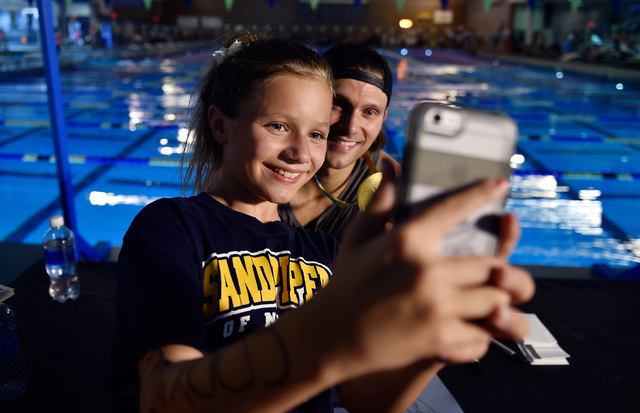 Anna Berry, 11, left, takes a selfie with Olympic swimmer gold medalist and Las Vegas resident Cody Miller after a Clark County key ceremony at the Desert Breeze Aquatic Center Monday, Aug. 29, 20 ...