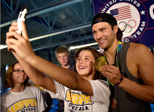 Raina Dasklova, left, takes a selfie with Olympic swimmer gold medalist and Las Vegas resident Cody Miller after a Clark County key ceremony at the Desert Breeze Aquatic Center Monday, Aug. 29, 20 ...