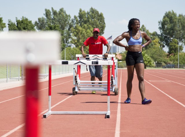 Uhunoma Osazuwa, right, and her coach Logan Taylor pick up hurdles during training at Myron Partridge Track Stadium at UNLV in Las Vegas on Tuesday, July 26, 2016. Osazuwa will be competing in the ...