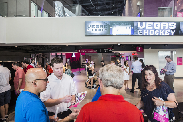 Sales representative Coal Miltenberger, left, discusses ticket options with attendees at T-Mobile Arena during an open house for Las Vegas' NHL expansion team on Monday, August 1, 2016, in Las Veg ...