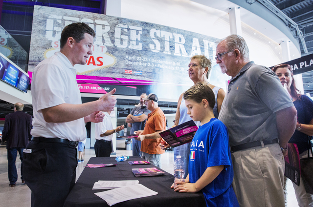 Sales representative Coal Miltenberger, left, discusses ticketing options with Jim and Alina Gardner and grandson Austin Leeb at T-Mobile Arena during an open house for Las Vegas' NHL expansion te ...