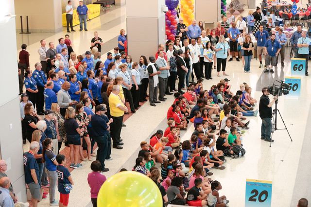 Children and team members listen to instructions prior to the start of the fourth annual Paper Plane Palooza event held at McCarran International Airport on Wednesday, Aug. 10, 2016. Children from ...