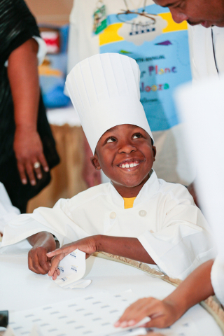 Team HMS member Ohmell Mims, 8, smiles as he receives a few pointers on plane construction during the fourth annual Paper Plane Palooza event held at McCarran International Airport on Wednesday, A ...