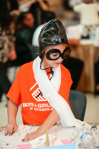 Team Commission Crew member Caddie Whitmire, 9, looks at instructions while building her plane during the fourth annual Paper Plane Palooza event held at McCarran International Airport on Wednesda ...