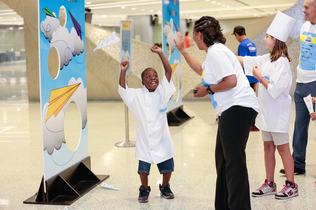 Team HMS member Ohmell Mims, 8, receives a high five during the fourth annual Paper Plane Palooza event held at McCarran International Airport on Wednesday, Aug. 10, 2016. Children from local Boys ...