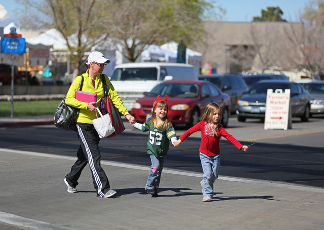 Sarah McCallum, from left, uses the crosswalk on Water Street with her daughters Rhea and Becca as a news conference on pedestrian safety efforts concludes nearby Thursday, March 5, 2015, in Hende ...