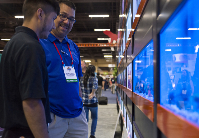 """Michael Crespo, right, and Rene Ruiz look at fish on """"Aquatic Terrace"""" during the SuperZoo Trade Show at the Mandalay Bay Convention Center on the Las Vegas Strip on Tuesday, Aug. 2, 2016. (Daniel ..."""