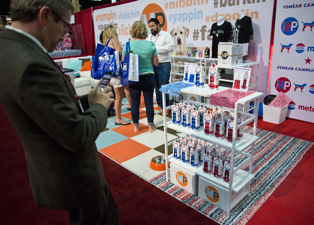 Adam Ertel takes a photo of pet waste bags featuring caricatured versions of presidential hopefuls on display during the SuperZoo Trade Show at the Mandalay Bay Convention Center on the Las Vegas  ...
