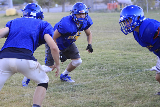 Moapa Valley High School center Cameron Larsen, center, runs through a drill during team practice at the school in Overton, Nev. on Wednesday, Aug. 17, 2016. Richard Brian/Las Vegas Review-Journal ...