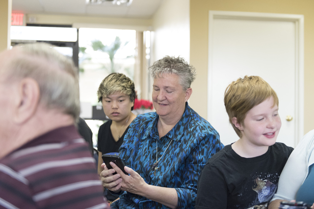 Pastor Charlotte Morgan, center, uses her smartphone during a smartphone usage class at Indigo Valley Church in Las Vegas on Friday, Aug. 5, 2016. Ande Morgan, left, and Malachi Grooms, right, loo ...