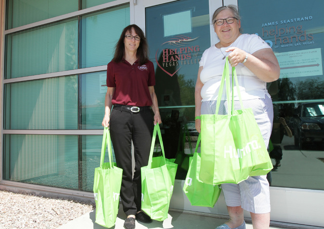Volunteer Mary Burns, 61, of Las Vegas, right, poses for a photo with Diana Barrett, Helping Hands of Vegas Valley pantry director, in front of their office in North Las Vegas, Thursday, Aug. 18,  ...