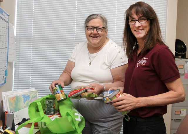 Volunteer Mary Burns, 61, of Las Vegas, left, poses for a photo with Diana Barrett, Helping Hands of Vegas Valley pantry director, at their office in North Las Vegas, Thursday, Aug. 18, 2016. Burn ...