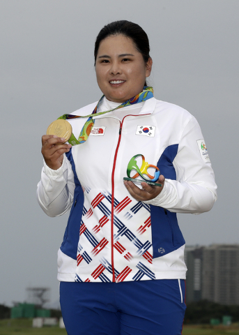 Inbee Park of South Korea, holds up her gold medal after the final round of the women's golf event at the 2016 Summer Olympics in Rio de Janeiro, Brazil, Saturday, Aug. 20, 2016. (AP Photo/Chris C ...