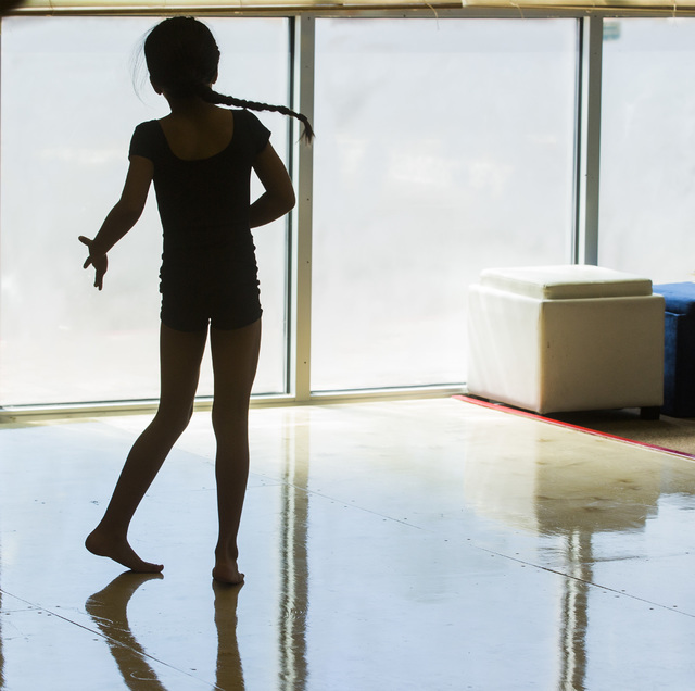 A younger dancer, seen in silhouette, tries out some moves during a weekday session of R.A.G.E. (Reaching Above Greater Expectations), former Cirque du Soleil dancer Tyrell Rolle's program for at- ...