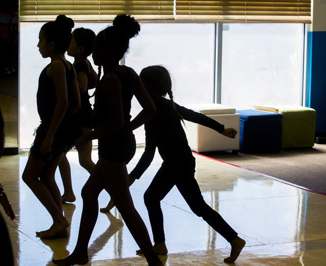 The summer light silhouettes girls dancing dancing at North Las Vegas' Studio 305 during the weekday R.A.G.E. (Reaching Above Greater Expectations) program founded by former Cirque du Soleil dance ...