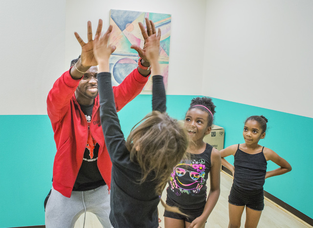 Former Cirque du Soleil dancer Tyrell Rolle high-fives participants in R.A.G.E. (Reaching Above Greater Expectations), part of the non-profit dance education organization now located at his new St ...