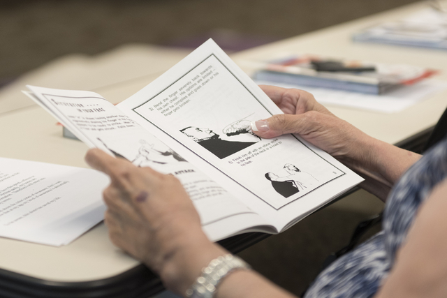A student reviews a booklet featuring the curriculum for Roland Rogers' self-defense class for senior citizens at Las Vegas police headquarters Friday, July 22, 2016. Jason Ogulnik/View
