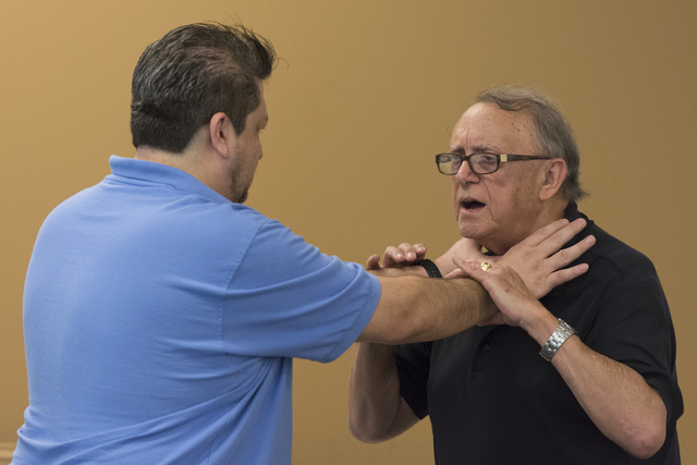 Instructor Roland Rogers, right, and volunteer Anthony Radel demonstrate self-defense moves during a class for senior citizens at Metropolitan Police Department headquarters on July 22, 2016. Jaso ...
