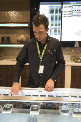 "Kenneth Yockey, dispensary agent with Las Vegas ReLeaf, shows marijuana samples during a walking tour of various medical marijuana dispensaries in Las Vegas' ""Green District"" Wednesday, April 20,  ..."